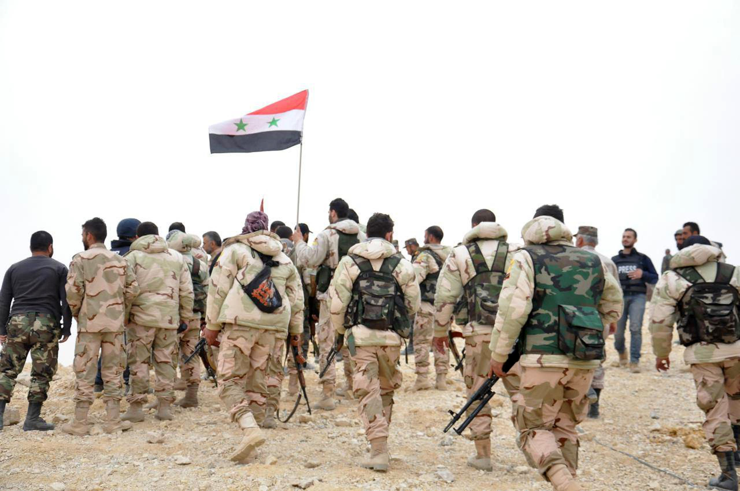 In this photo released by the Syrian official news agency SANA, Syrian soldiers gather around a Syrian national flag in Palmyra, Syria, Sunday, March 27, 2016. (AP)