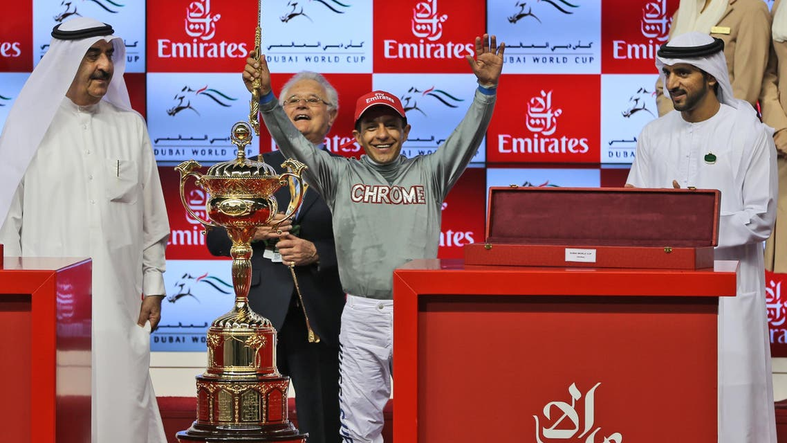Victor Espinoza, jockey of California Chrome from the U.S. celebrates after winning the U.S. $ 10,000,000 Dubai World Cup horse racing at the Meydan Racecourse as the Dubai Crown Prince, Sheikh Hamdan Bin Mohammed Al Maktoum, right, attends, in Dubai AP