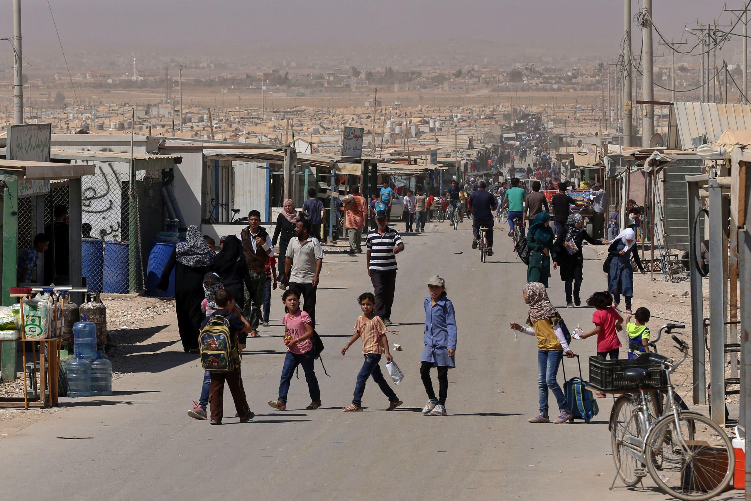In this Thursday, Oct. 1, 2015 photo, Syrian refugees stroll on the main street of the U.N.-run Zaatari refugee camp near Mafraq, northern Jordan. AP