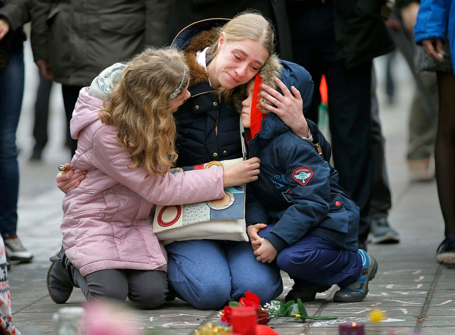 A woman consoles her children at a street memorial following Tuesday's bomb attacks in Brussels, Belgium, March 23, 2016. REUTERS