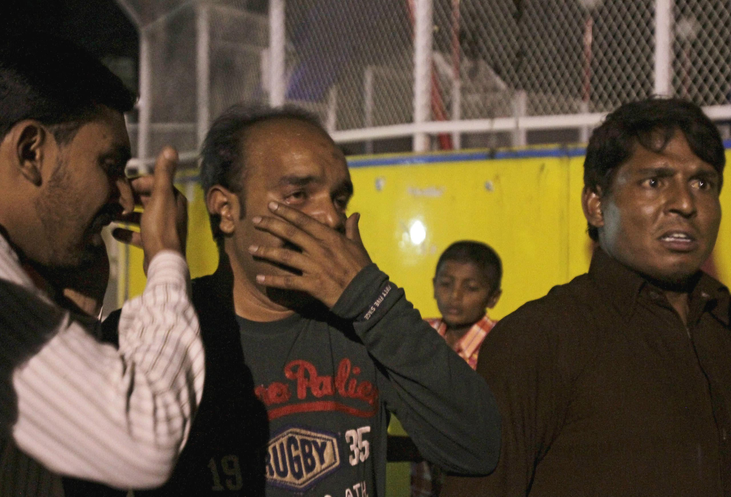Men mourn the death of their relatives after a blast outside a public park in Lahore, Pakistan. (Reuters)