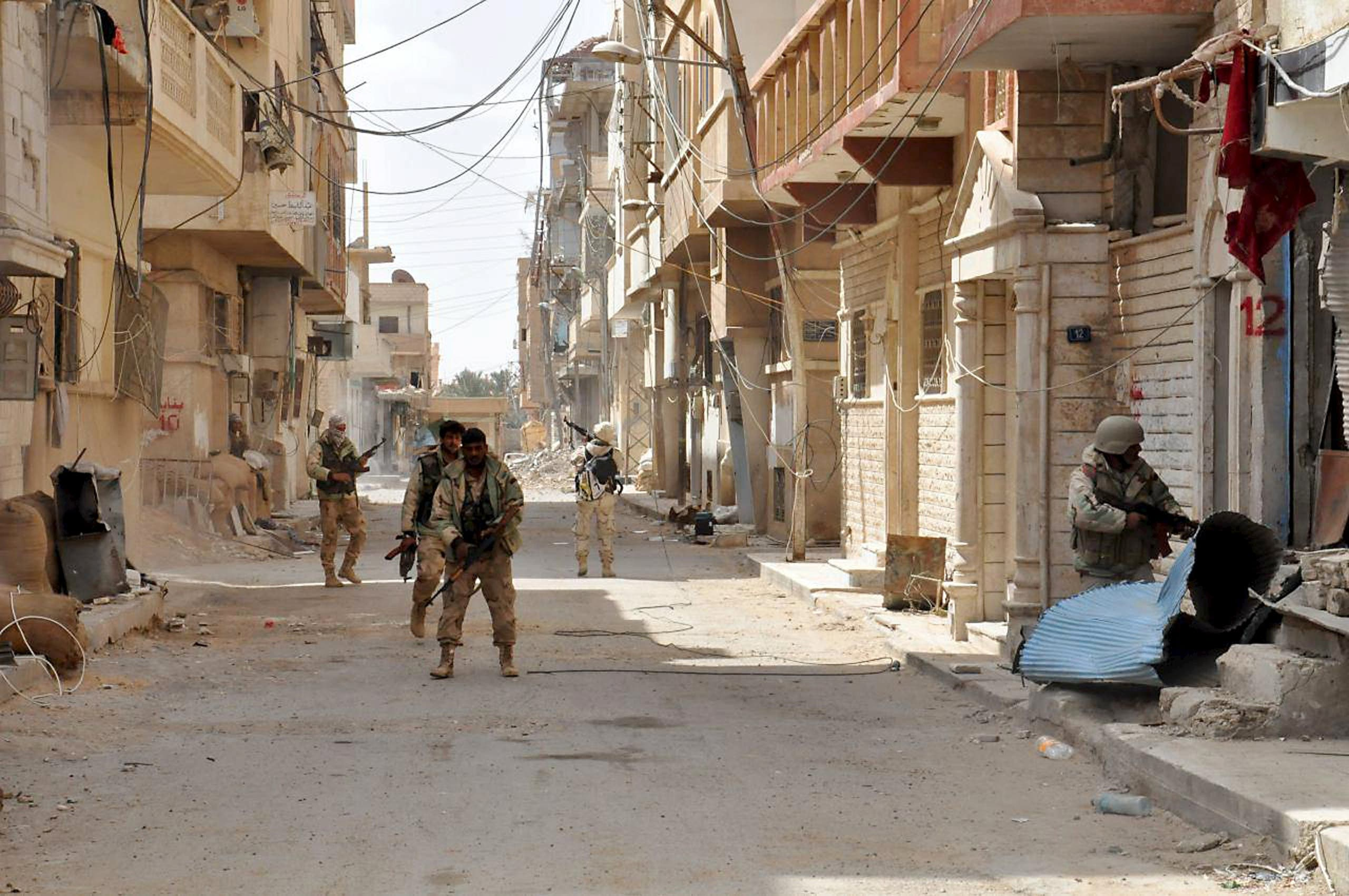 Forces loyal to Syria's President Bashar al-Assad walk with their weapons in Palmyra city after they recaptured it, in Homs Governorate on March 27, 2016. (Photo courtesy: SANA)