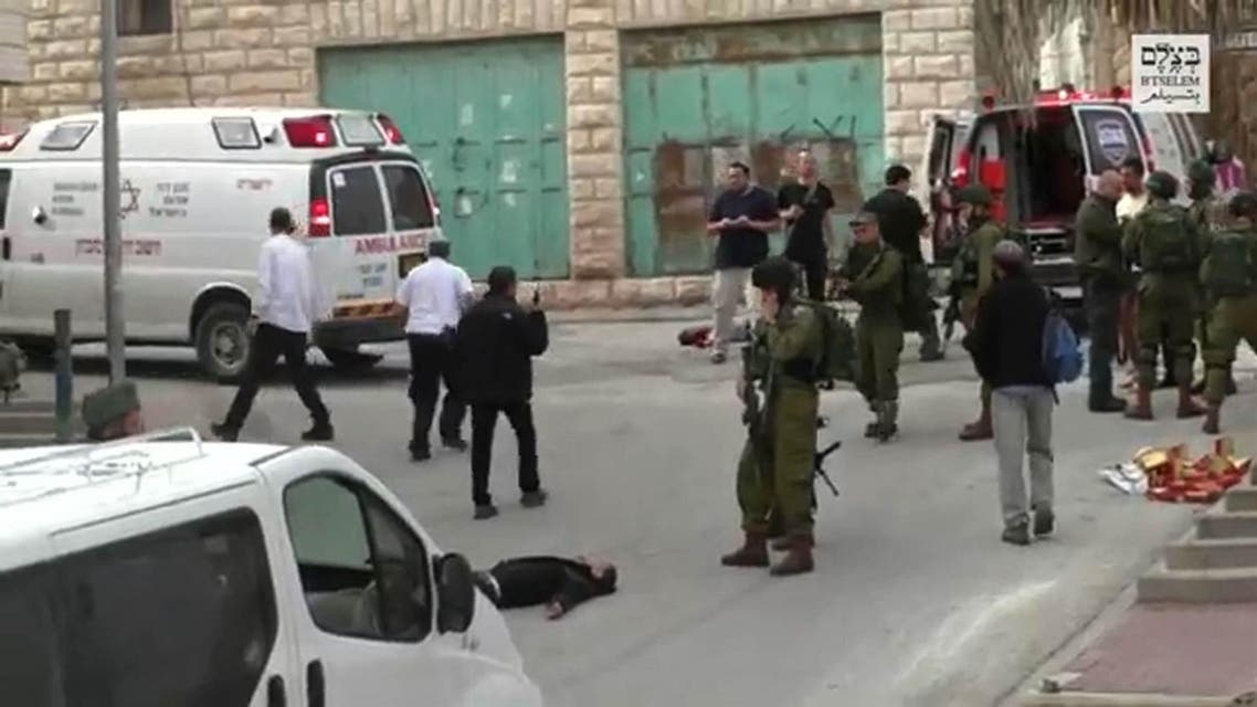In this still from a video released by an Israeli human rights group, an Israeli soldier aims his weapon before apparently shooting and killing a wounded Palestinian assailant laying on the ground in the West Bank town of Hebron. (Photo courtesy: B'Tselem via AFP)