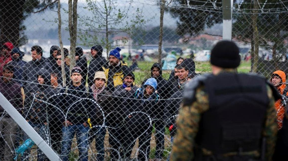 Migrants behind the fence at the Macedonian-Greek border on March 27, 2016, where thousands are stranded by the Balkan border blockade (AFP)