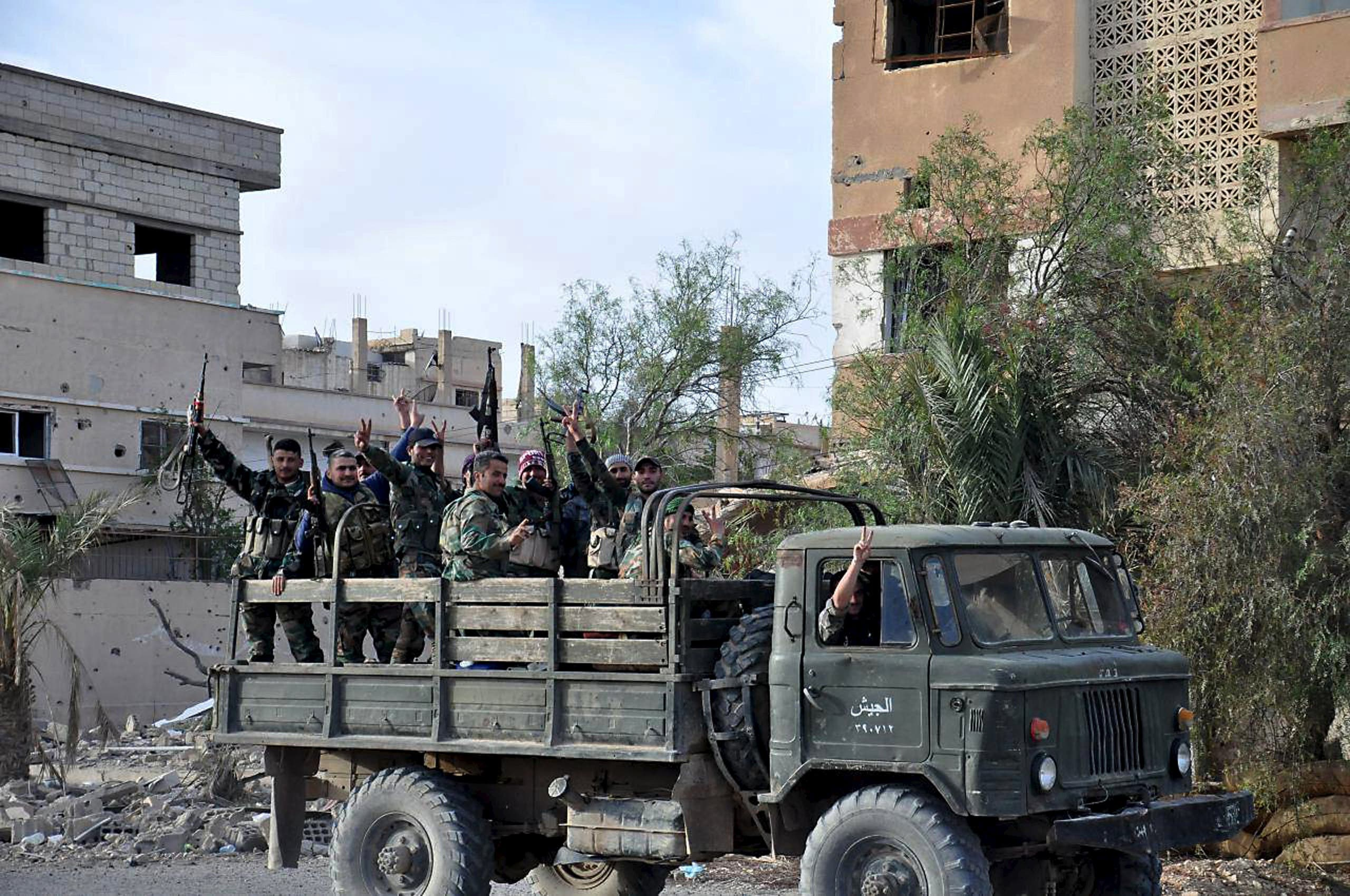 Forces loyal to Syria's President Bashar al-Assad flash victory signs while riding on the back of a military truck in Palmyra city, in Homs Governorate on March 27, 2016. (Photo courtesy: SANA)