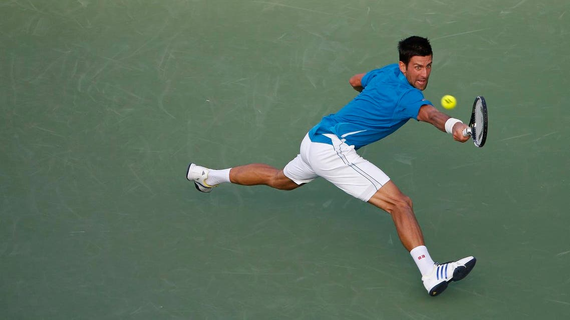 Novak Djokovic reaches for a backhand against Joao Sousa (not pictured) during day six of the Miami Open at Crandon Park Tennis Center. Djokovic won 6-4, 6-1. Mandatory Credit: Geoff Burke-USA TODAY Sports