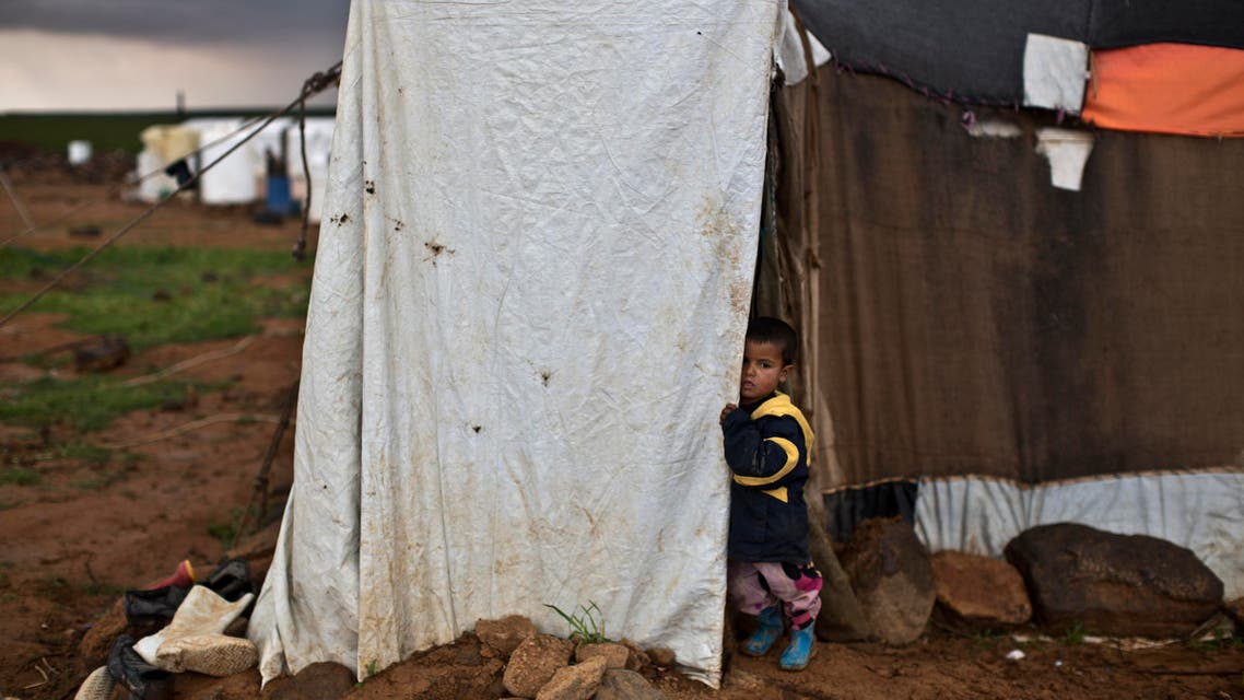 A Syrian refugee stands at the doorway of his family's tent at an informal tented settlement near the Syrian border, on the outskirts of Mafraq, Jordan, Monday, March 28, 2016. (AP Photo/Muhammed Muheisen)