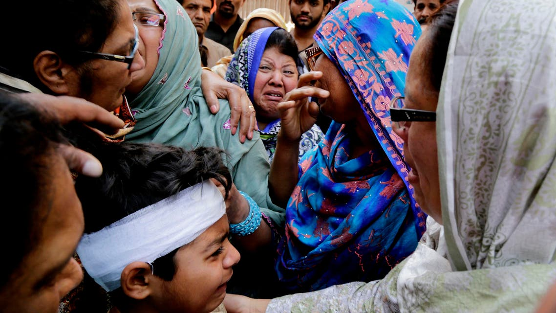 Eric John, bottom, who survived Sunday's attack, cries during the funeral of his cousin killed, in Lahore, Pakistan, Monday, March 28, 2016. The death toll from a massive suicide bombing targeting Christians gathered on Easter in the eastern Pakistani city of Lahore rose on Monday as the country started observing a three-day mourning period following the attack. (AP Photo/K.M. Chaudary)