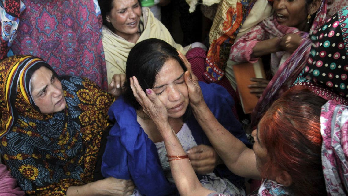 Family members comfort a woman mourns the death of a relative, who was killed in a blast outside a public park on Sunday, during funeral in Lahore, Pakistan, March 28, 2016. REUTERS/Mohsin Raza