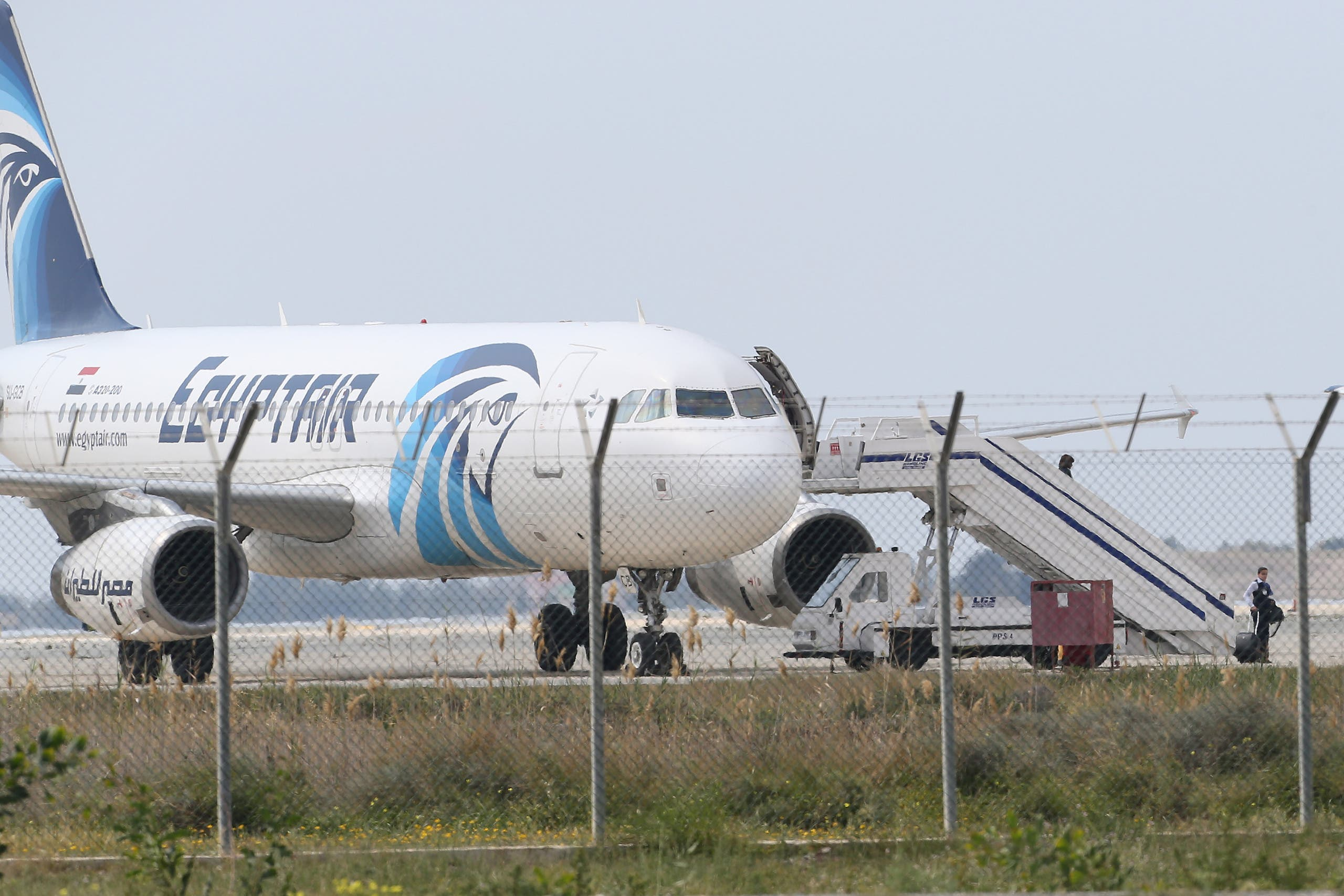 Passengers leave the hijacked aircraft of Egyptair after landing at Larnaca airport Tuesday, March 29, 2016 in Larnaca, Cyprus. AP