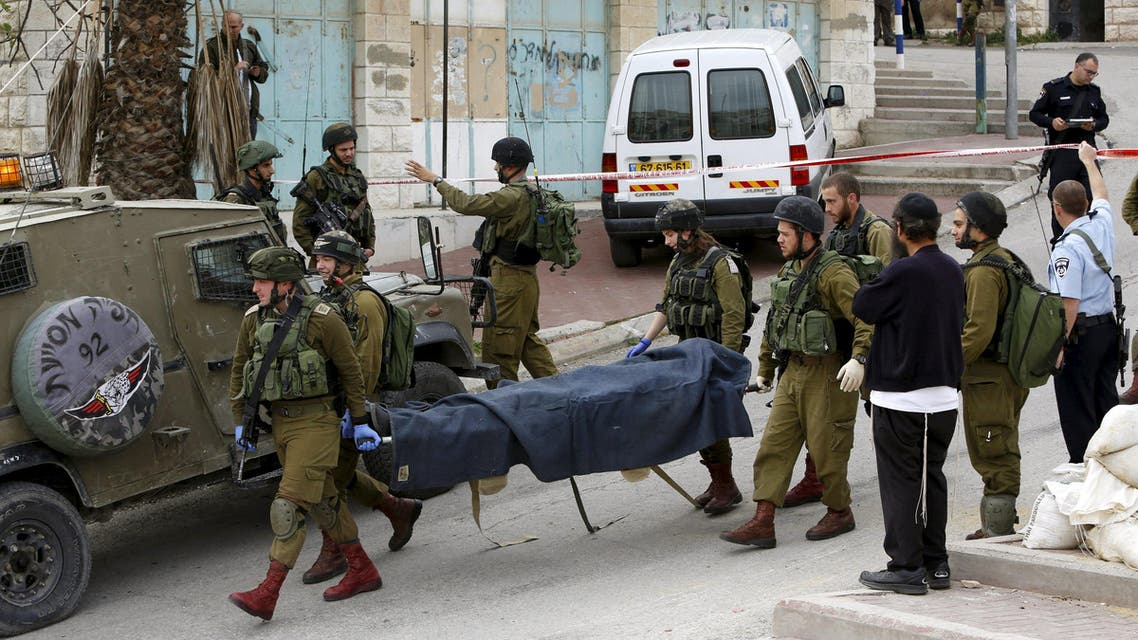 Israeli soldiers carry the dead body of one of two Palestinians, whom the Israeli military said were shot dead by Israeli troops after they attacked an Israeli soldier, in Tal Rumaida in the West Bank city of Hebron March 24, 2016. REUTERS/Mussa Qawasma