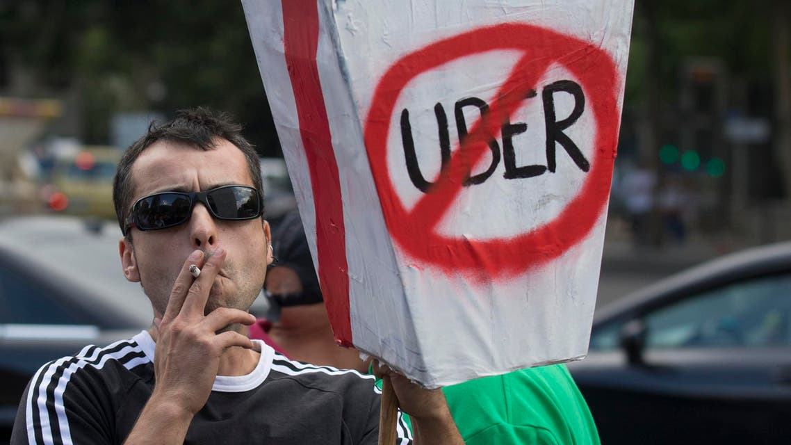 In this June 11, 2014 file photo, a demonstrator carries a mock coffin with a message reading 'They want to kill us - Uber' during a 24 hour taxi strike and protest in Madrid, Spain against unregulated competition from private companies, in particular, Uber. AP