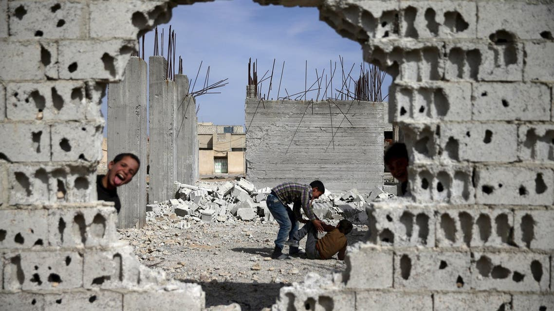 Boys play near rubble of damaged buildings in the rebel held besieged town of Douma, eastern Damascus suburb of Ghouta, Syria March 19, 2016. REUTERS/Bassam Khabieh