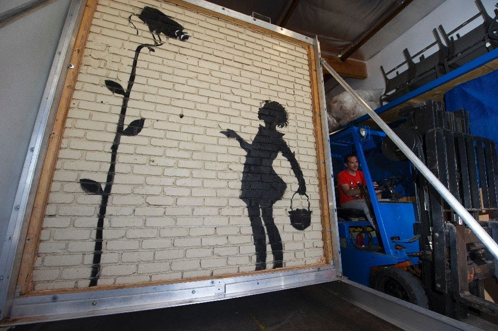 In December 2015, Julien's Auctions offered Banksy's 'Flower Girl', a piece painted on a gas station wall in Hollywood (AFP)