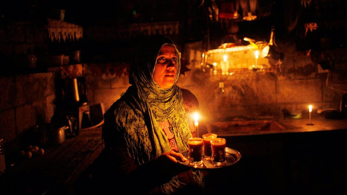 A Palestinian woman holds coffee inside her house during power cuts in Khan Younis in the southern of Gaza Strip March 15, 2014. (File photo: Reuters)