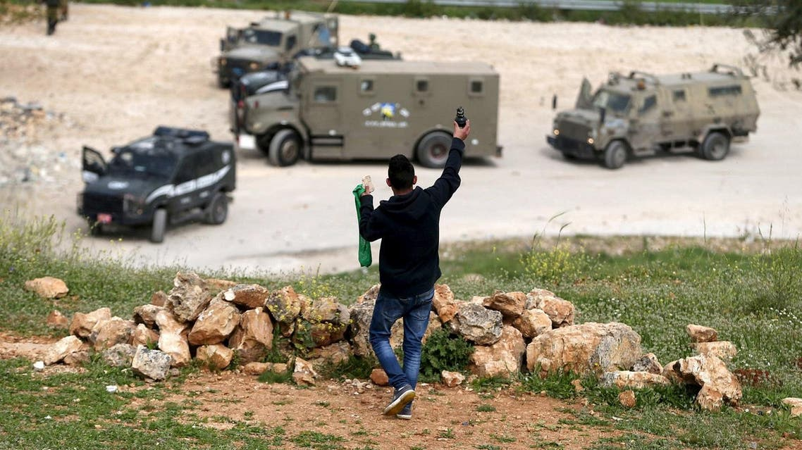 Palestinian protester holds up an unspent tear gas grenade fired by Israeli troops as he stands in front of the troops during clashes, near Israel's Ofer Prison, near the West Bank city of Ramallah. (Reuters)