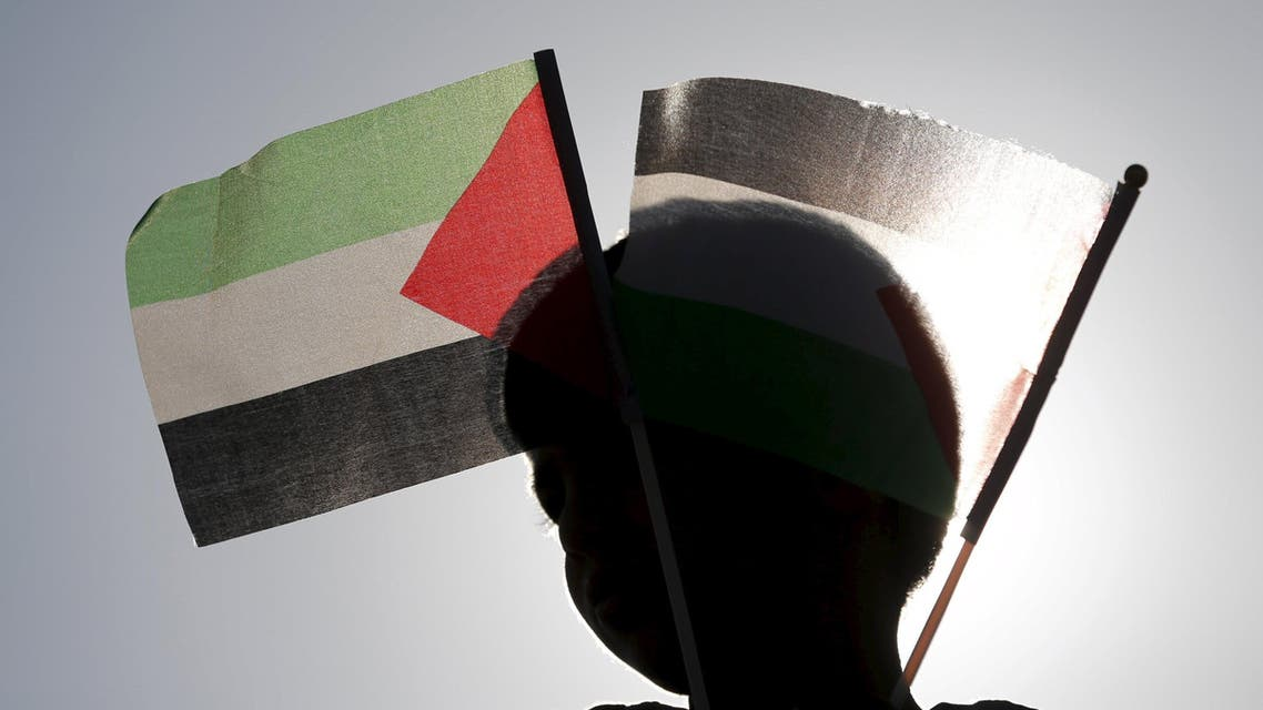 A Bedouin boy holds Palestinian flags as he takes part in a rally marking Land Day in Umm el-Hiran, an unrecognised Bedouin village near southern Israeli city of Beersheba, March 30, 2016. March 30 marks Land Day, the annual commemorations of the killing by police of six Arab citizens in 1976 during protests against land confiscations in northern Israel's Galilee region. REUTERS/Amir Cohen