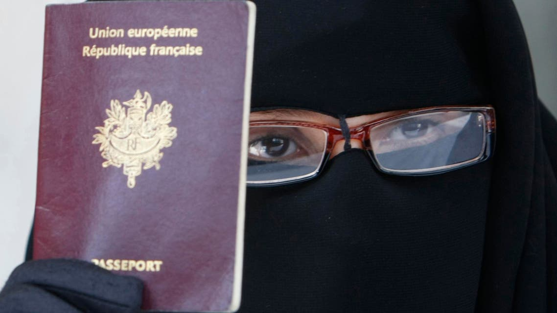 This May 18 2010 file photo shows a woman, who gave her name as Najat, holding her passport during a press conference in Montreuil, east of Paris. AP