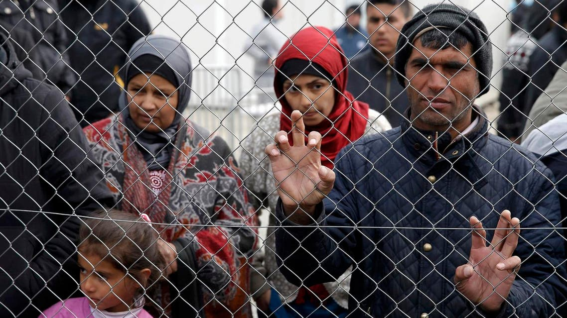 Migrants and refugees stand by a fence at a makeshift camp at the Greek-Macedonian border near the village of Idomeni, Greece, March 27, 2016. REUTERS