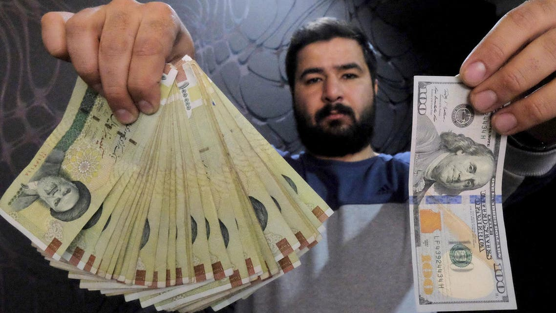 [Window Title] Enter name of file to save to…  [Content] A money changer poses for the camera with a U.S hundred dollar bill (R) and the amount being given when converting it into Iranian rials (L), at a currency exchange shop in Tehran's business district, Iran, January 20, 2016.  (Reuters) The file name is not valid.  [OK]