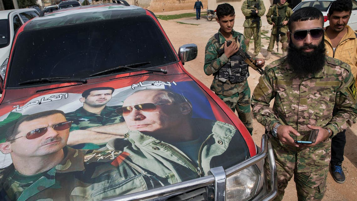 Syrian solders and Russian solders, who escort a group of journalists in the background, stand near a car covered by collage showing photos of faces of Russian President Vladimir Putin, right, Syrian President Bashar al-Assad,