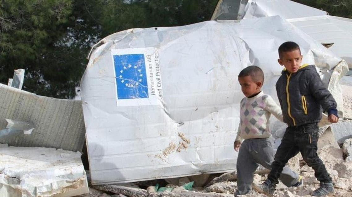 Palestinian boys walks past the remains of their family's dwelling, that was funded by the EU's humanitarian arm, after it was demolished by Israeli forces, near the West Bank village of Al-Eizariya, near east of Jerusalem January 21, 2016 (Reuters)