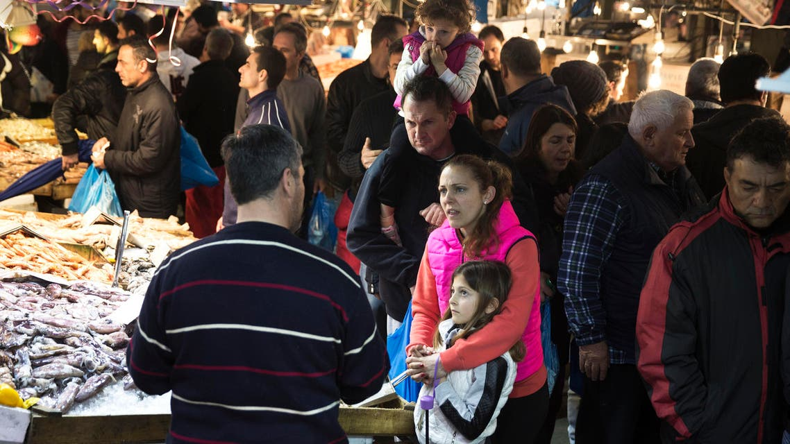 A family buys seafood at the fish market in Athens Monday, March 14, 2016. (AP)
