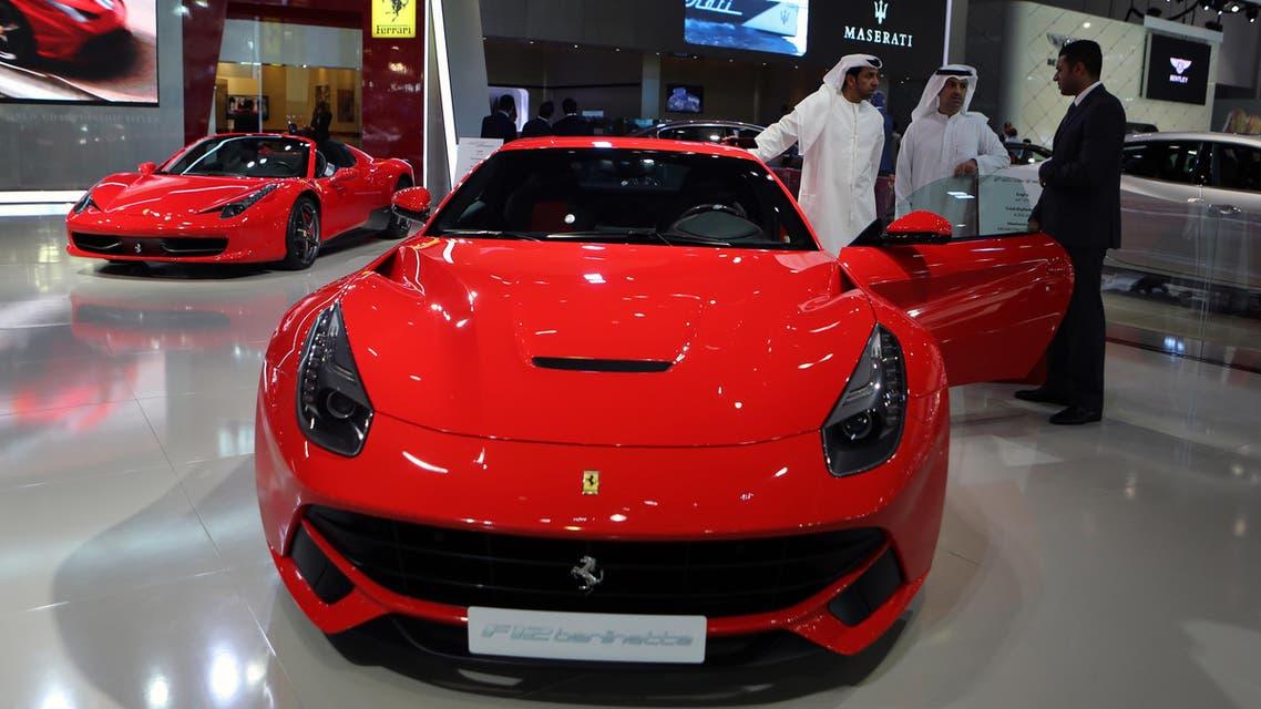 Emirati visitors examine the Ferrari F12 berlinetta at the Dubai International Motor Show in Dubai, United Arab Emirates. (AP)