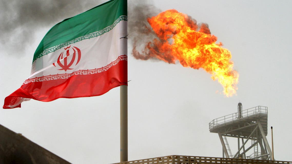 A gas flare on an oil production platform in the Soroush oil fields is seen alongside an Iranian flag in the Persian Gulf, in this July 25, 2005 file photo. REUTERS/Raheb Homavandi/Files