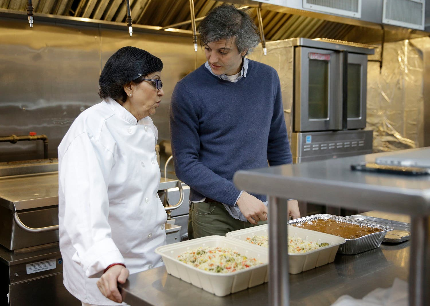Rachana Rimel, a Nepalese refugee, left, talks with head chef Juan Suarez de Lezo while they cook in New York, Tuesday, March 29, 2016. A food delivery service is offering New Yorkers the chance to try some food cooked by some unusual chefs. All seven employees at Eat Offbeat are either refugees or asylum-seekers who fled their home countries. They're cooking foods from those places, including Iraq and Nepal. (AP)