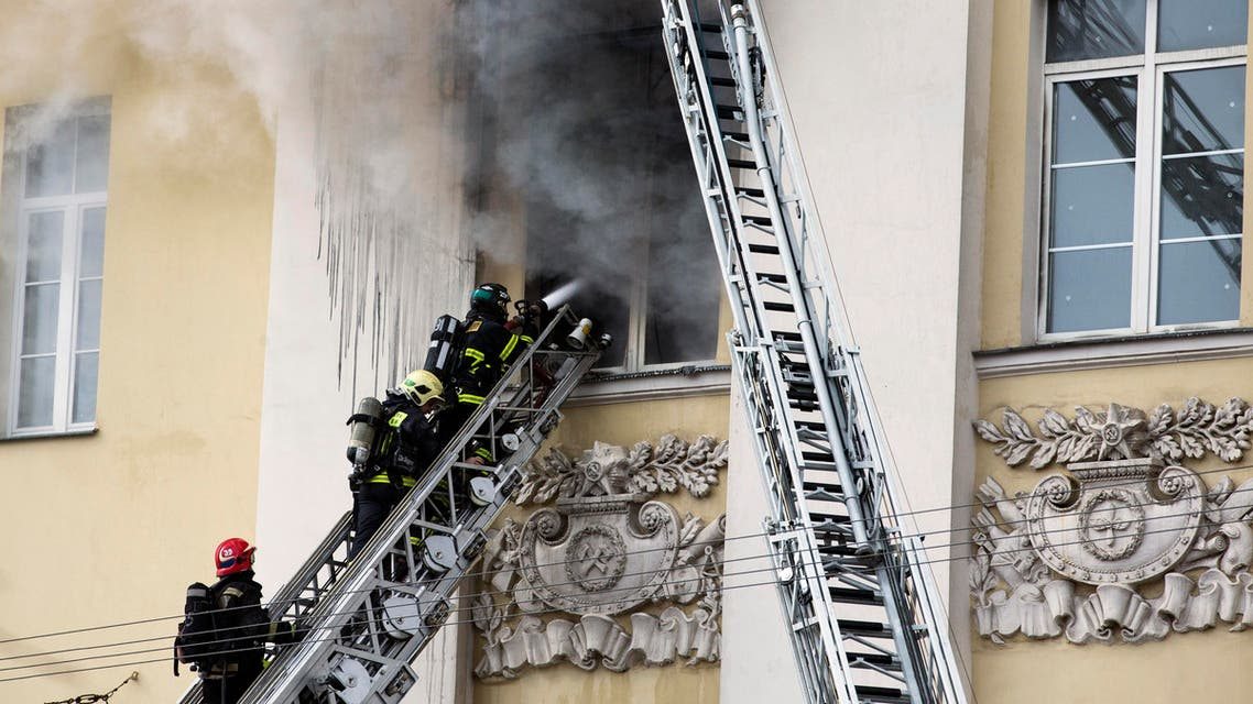 Firefighters climb to put out a blaze at a building of Russian Defense Ministry in Moscow, Russia, Sunday, April 3, 2016. A building of the Russian Defense ministry is on fire in central Moscow, the city's law enforcement bodies told Russian news agency TASS on Sunday. (AP Photo/Ivan Sekretarev)