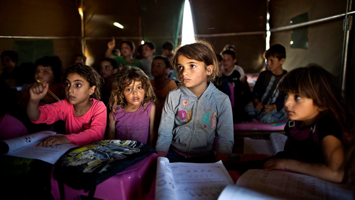 FILE - In this Tuesday, Aug. 11, 2015 file photo, Syrian refugee children attend a class at a makeshift school set up in a tent at an informal tented settlement near the Syrian border on the outskirts of Mafraq, Jordan. The U.N. agency for children says more than 80 percent of Syria's children have been harmed by the five-year-old conflict, including growing numbers forced to work, join armed groups or marry young because of widening poverty. (AP Photo/Muhammed Muheisen, File)