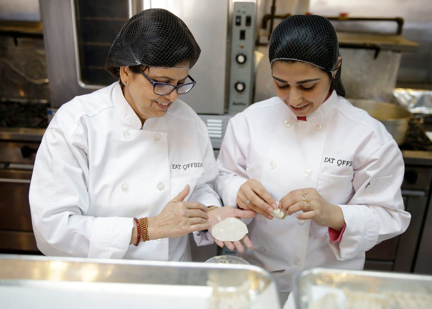 Rachana Rimel, left, and Dhuha Jasim make nepalese dumplings in New York, Tuesday, March 29, 2016. A food delivery service is offering New Yorkers the chance to try some food cooked by some unusual chefs. All seven employees at Eat Offbeat are either refugees or asylum-seekers who fled their home countries. They're cooking foods from those places, including Iraq and Nepal. (AP)