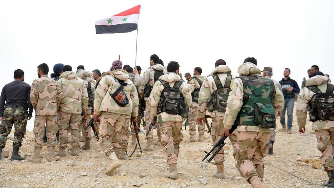 In this photo released by the Syrian official news agency SANA, Syrian soldiers gather around a Syrian national flag in Palmyra, Syria, Sunday, March 27, 2016. Syrian state media and an opposition monitoring group say government forces backed by Russian airstrikes have driven Islamic State fighters from the historic central town of Palmyra, held by the extremists since May. (SANA)