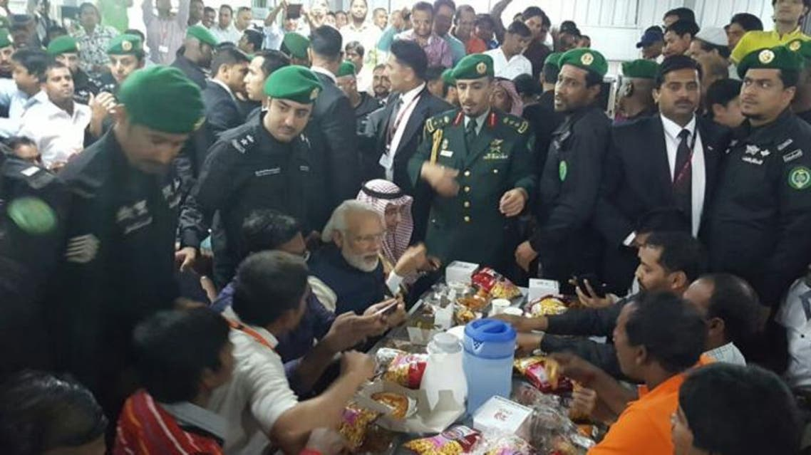 Indian Prime Minister Narendra Modi shares snacks with Indian workers of Larson and Tourbo at their camp on the outskirts of Riyadh on Saturday. (Photo courtesy: Saudi Gazette)