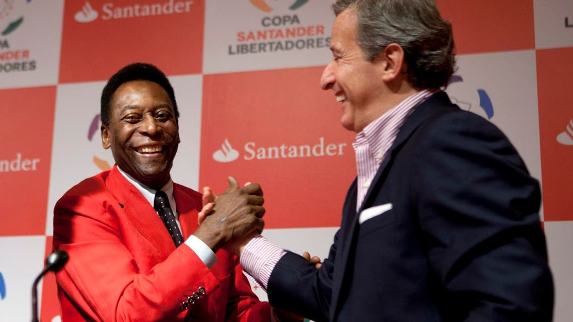 """In this Wednesday, June 22, 2011 file photo, Juan Pedro Damiani, president of Uruguay's Penarol soccer club, right, shakes hands with Brazilian soccer legend Pele after a news conference in Sao Paulo, Brazil. A FIFA judge who helped ban Sepp Blatter for financial misconduct is now under investigation by his ethics committee colleagues after being named in an international probe of offshore accounts. The FIFA ethics prosecution chamber said Monday, April 4, 2016 that it """"opened a preliminary investigation to review the allegations"""" linked to lawyer Juan Pedro Damiani of Uruguay. Damiani was identified in reports Sunday by international media who got a vast trove of data and documents leaked from a Panama law firm about evading tax and hiding assets through offshore accounts. (AP Photo/Victor R. Caivano, file)"""