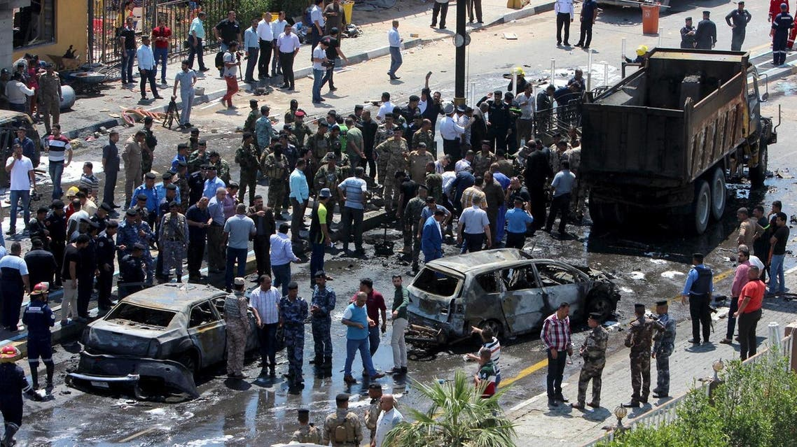 Iraqi security forces with people gather at the site of a car bomb attack in Basra. (Reuters)
