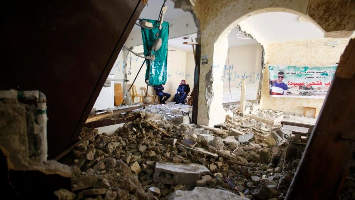 Palestinians sit inside the home of Ehab Maswada, seen on the poster, that was demolished by the Israeli army in the West Bank city of Hebron, Thursday, March 31, 2016. (File photo: AP)