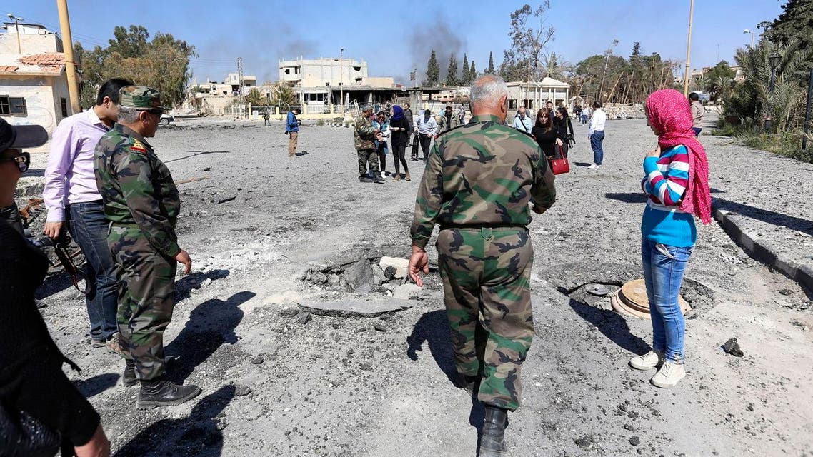 In this picture taken Friday, April 1, 2016, Syrian soldiers explain the military operation to clear Palmyra to journalists, in the ancient city of Palmyra in the central city of Homs, Syria. Explosions rocked the ancient town of Palmyra on Friday and on the horizon, black smoke wafted behind its majestic Roman ruins, as Syrian army experts carefully detonated hundreds of mines they say were planted by Islamic State militants before they fled the town. (AP Photo)