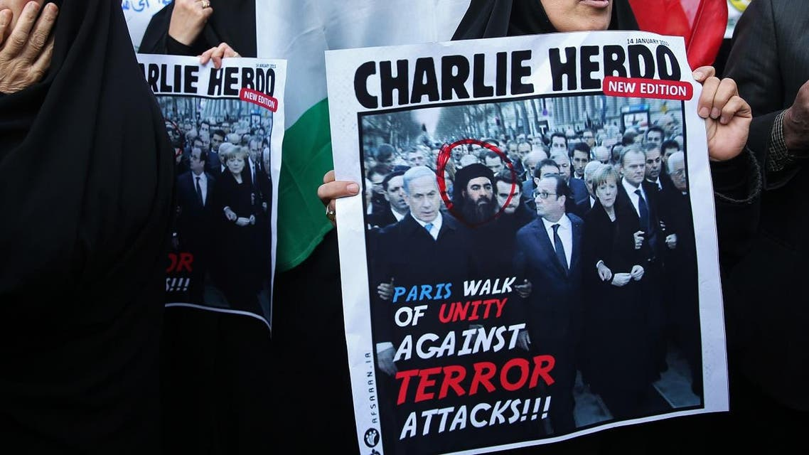 An Iranian demonstrator holds a satirical poster cover mocking the French weekly Charlie Hebdo which shows the Paris rally but adds a portrait of the ISIS leader Abu Bakr al-Baghdadi among the world leaders. (File photo: AP)