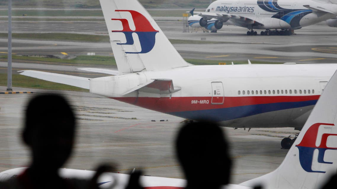 In this photo taken on Saturday, March 5, 2016, Malaysia men are silhouetted against taxied Malaysia Airlines' planes in Kuala Lumpur International Airport in Sepang, Malaysia. (AP)