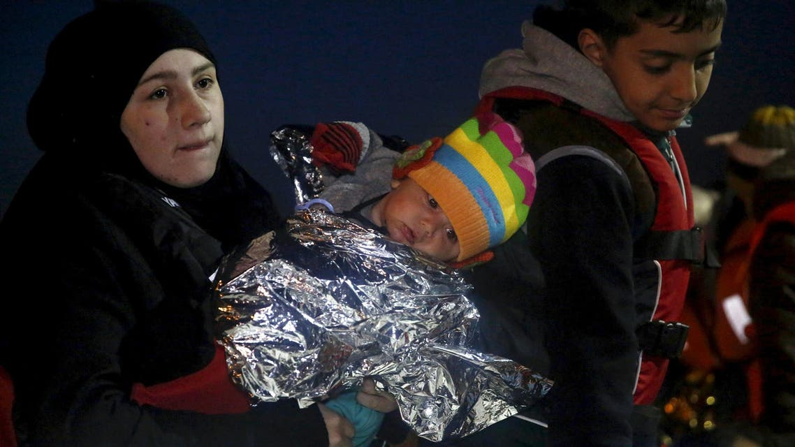 A woman holds her child as refugees and migrants wait to disembark a Greek Coast Guard vessel at the port of Mytilene on the Greek island of Lesbos, following a rescue operation at open sea, April 3, 2016. AP
