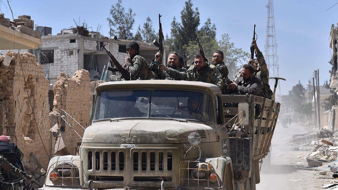 Syrian soldiers celebrate their victory against the Islamic State group in Qaryatain, Syria, Monday, April 4, 2016. AP