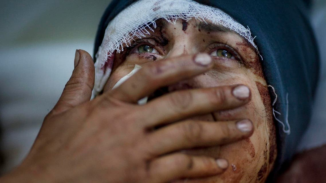 A woman named Aida cries as she recovers from severe injuries after the Syrian army shelled her house in Idlib, northern Syria, March 10, 2012. (AP)