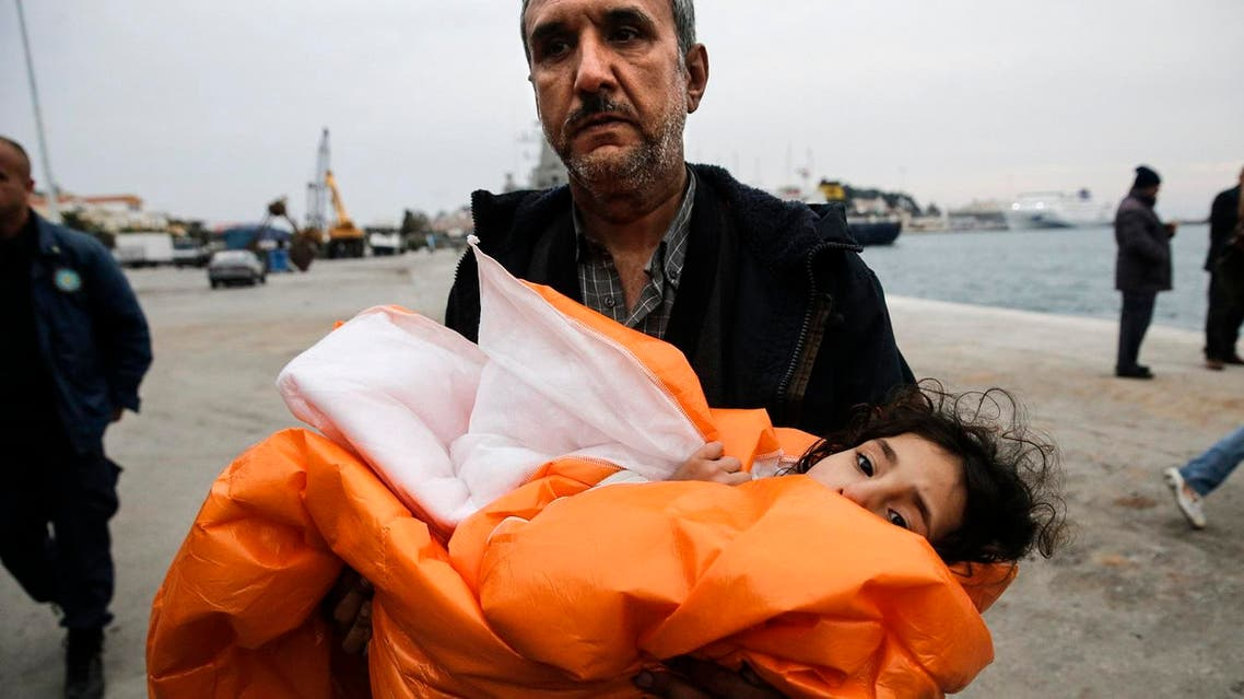 A Syrian refugee carries his daughter covered with a blanket, after being rescued at open sea, as they arrive at the port of Mytilene on the Lesbos island. (Reuters)