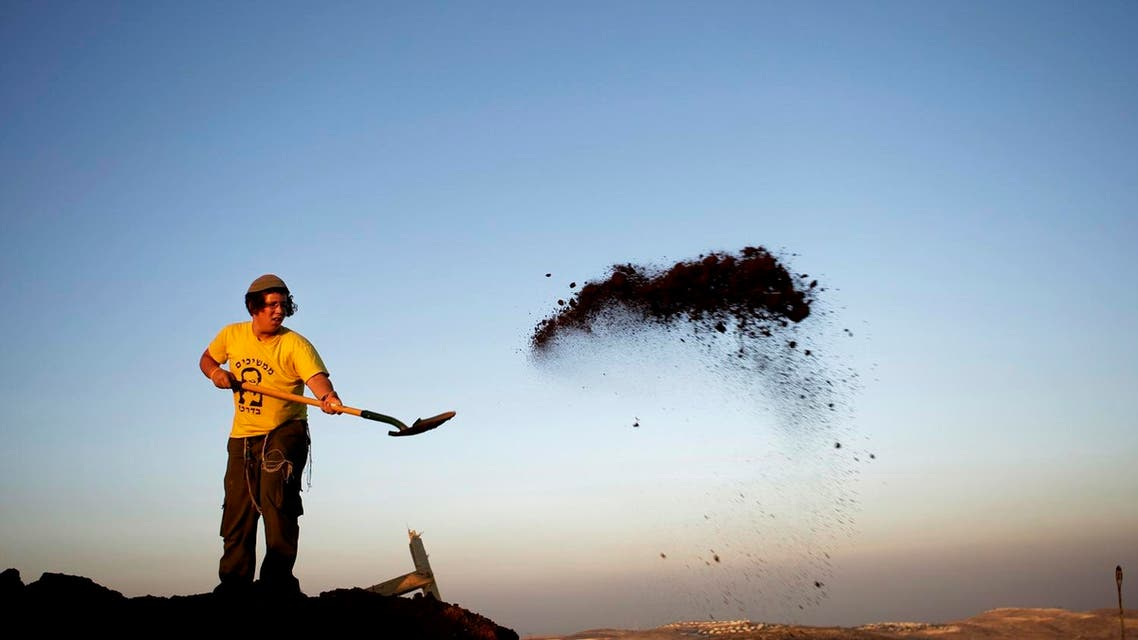 A Jewish settler removes soil from around structures demolished earlier by Israeli troops in the illegal West Bank outpost of Ramat Migron, a hilltop site near the West Bank city of Ramallah, Wednesday, June 3, 2009. (AP)