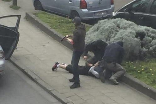 Police officers detain a suspect during a raid in which fugitive Mohamed Abrini was arrested in Anderlecht, near Brussels, Belgium, April 8, 2016 in this still image taken from video. REUTERS/Sebastien Dana-Kamran via Reuters