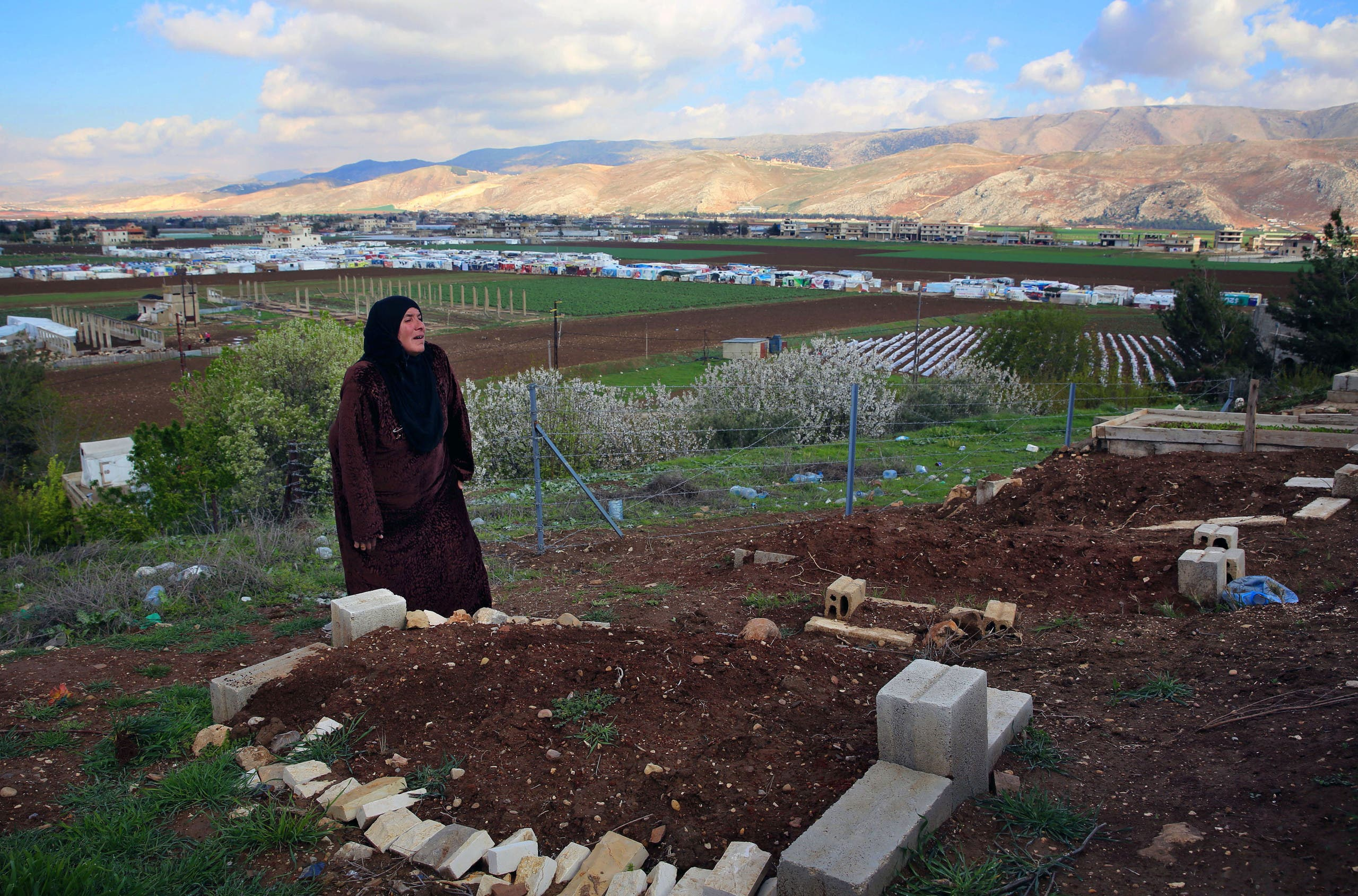 In this Tuesday, March 29, 2016 photo, Syrian refugee Saada Khalaf, 45, who fled from the city of Homs, Syria, cries near the grave of her husband Ali Jomaa, in the eastern village of Dalhamyeh, in the Bekaa valley, Lebanon.