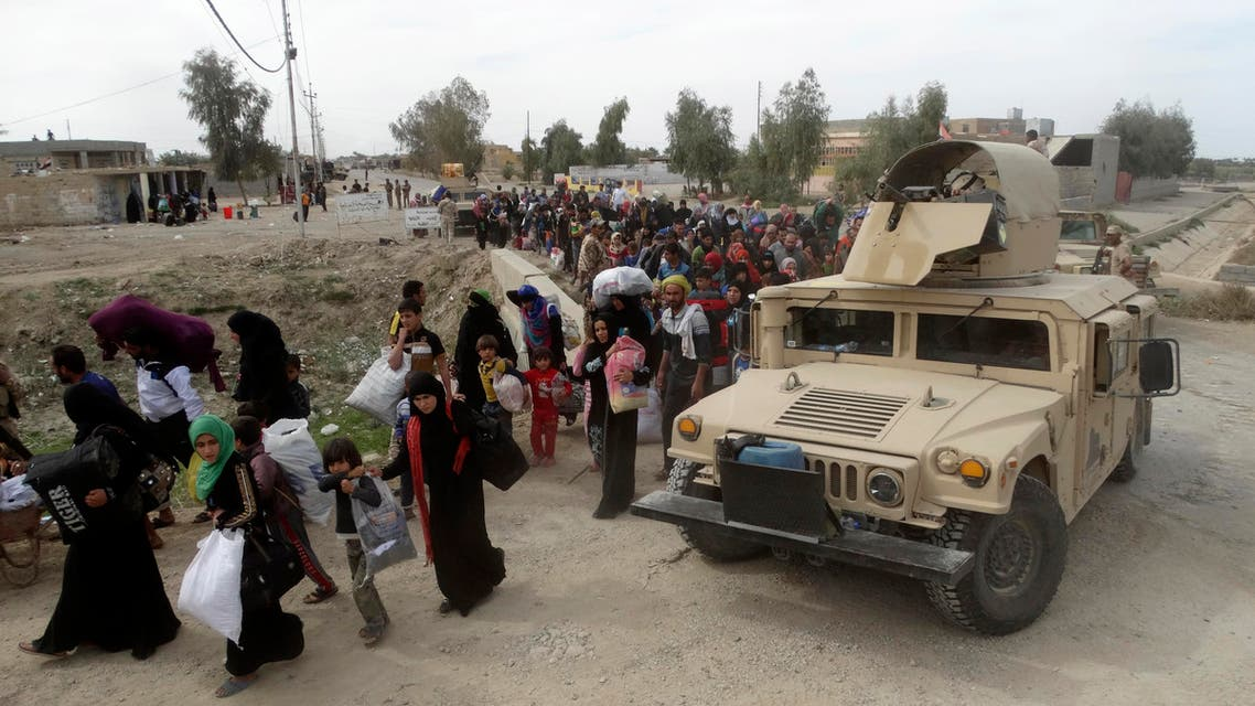In this Wednesday, March 9, 2016 photo, civilians leave their houses after clashes between Iraqi Security forces and Islamic State group extremists outside Ramadi, 70 miles (115 kilometers) west of Baghdad, Iraq. (AP)