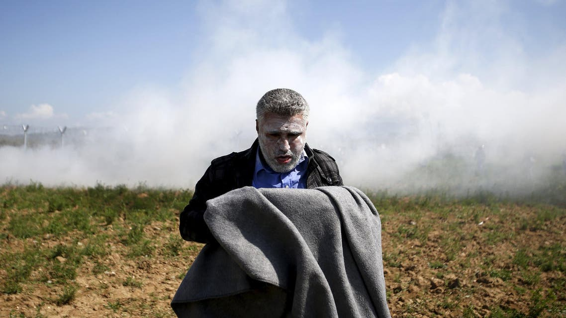A migrant catches his breath after inhaling teargas thrown by Macedonian police on a crowd of more than 500 refugees and migrants protesting next to a border fence at a makeshift camp at the Greek-Macedonian border near the village of Idomeni, Greece, April 10, 2016. reuters